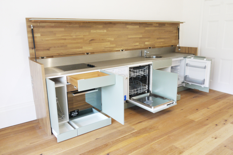 photograph of an innovative sideboard kitchen with lift up lid in the open position, showing integrated appliances and storage