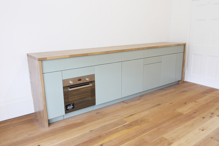 photograph of an innovative sideboard kitchen with lift up lid in the closed position, showing integrated appliances and storage