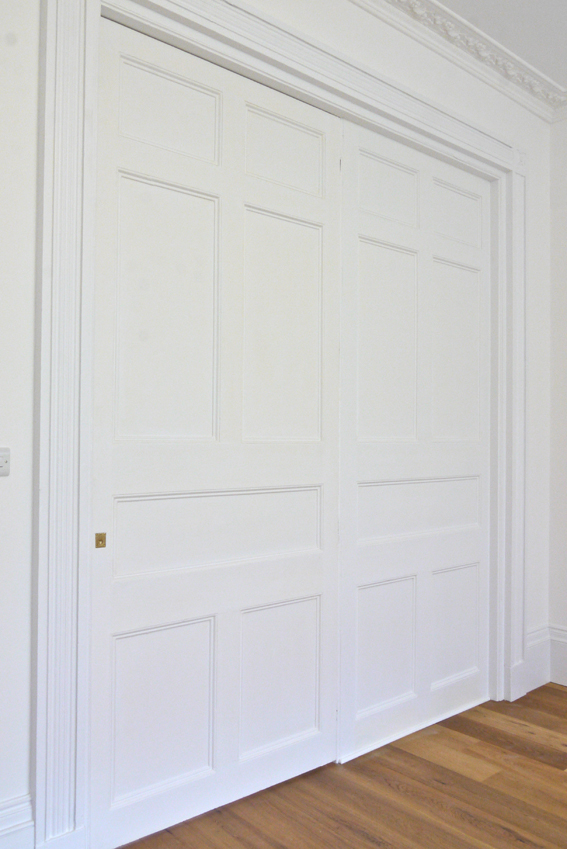 view of a large, white painted panelled timber door
