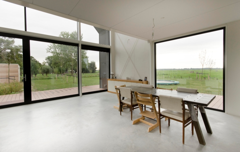 a photograph of a bright modern interior showing views out of large windows with dining room furniture set on a polished concrete floor