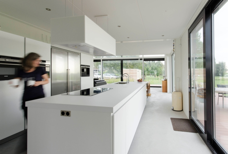 a photograph of a bright modern kitchen interior with views out of large windows and bright white kitchen units and modern appliances.