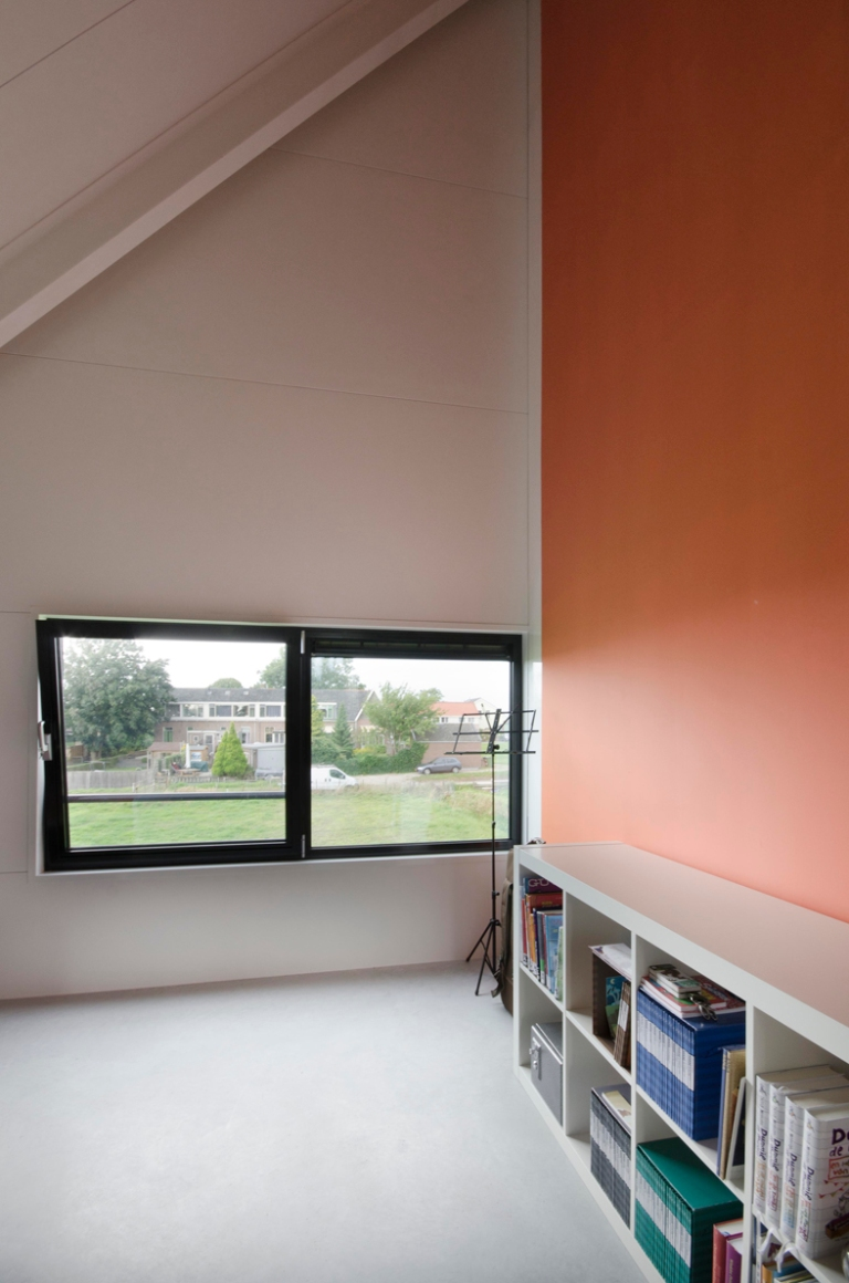 a photograph of a modern bedroom interior with a feature wall painted in dark orange and showing how the room nestles into the roof pitch, providing a beautifully high ceiling.