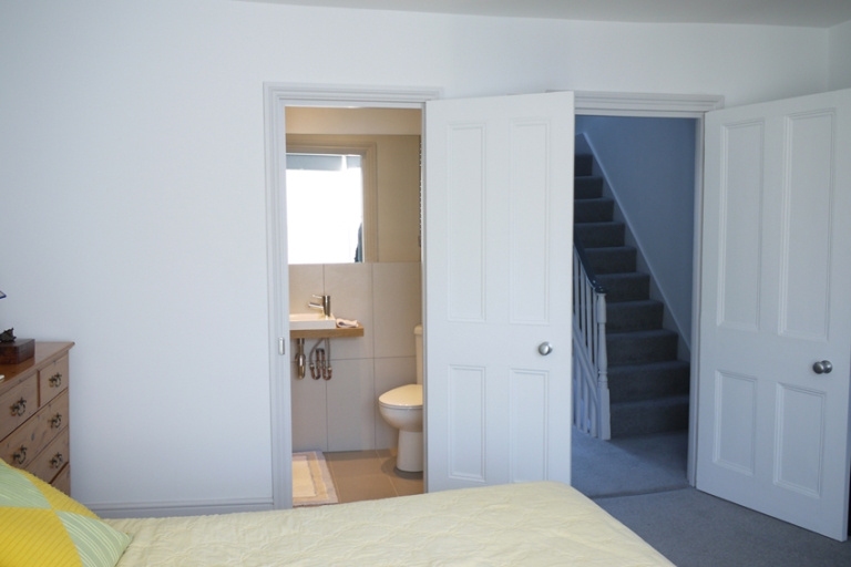 A photograph of the master bedroom at Dorset Place showing the cleverly inserted ensuite, designed to be as discrete as possible.