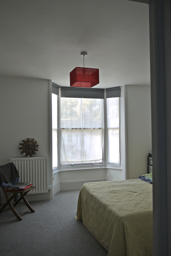 A photograph of the master bedroom at Dorset Place showing the view from the door out of the renovated bay window.